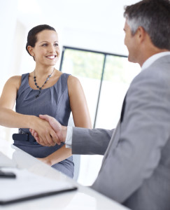 Smiling young businesswoman shaking hands with a male executive while sitting at a desk